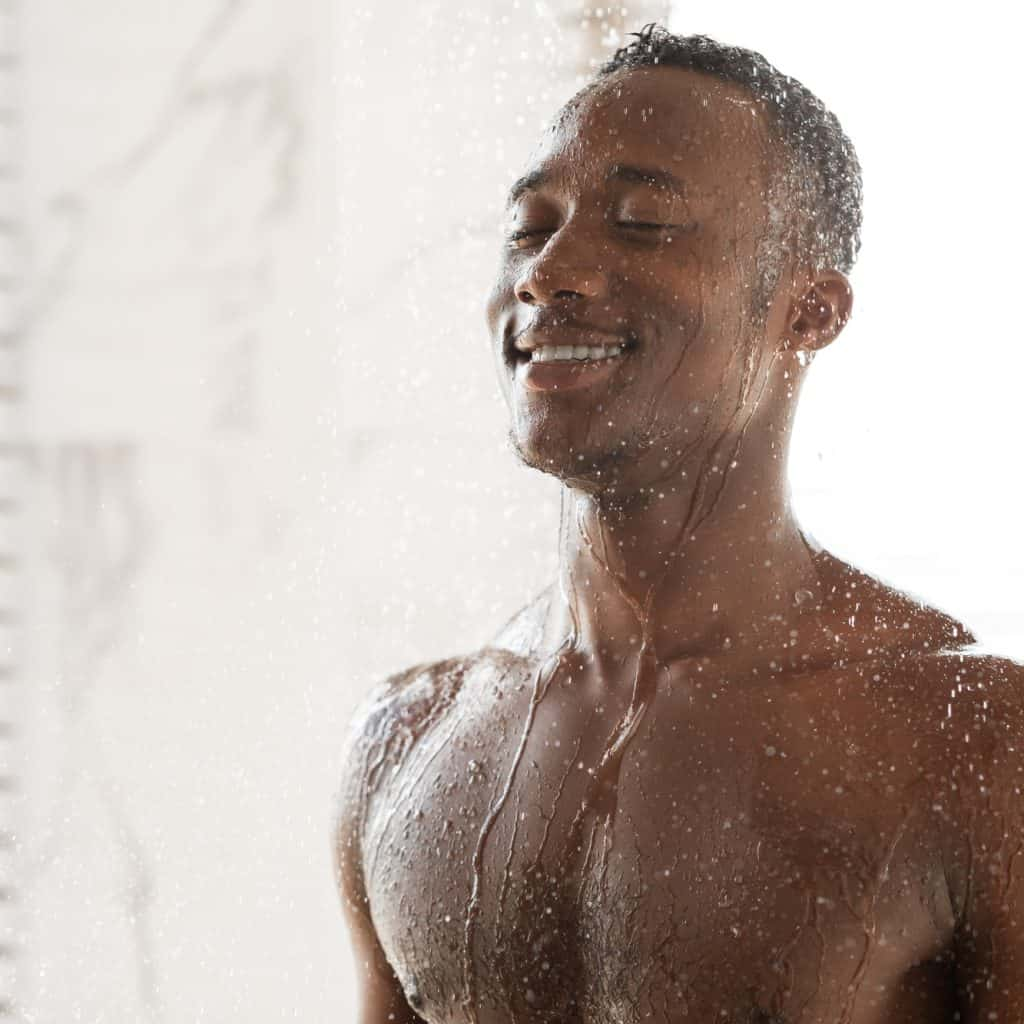 Happy African Man Taking Cold Shower Refreshing In Morning Indoor